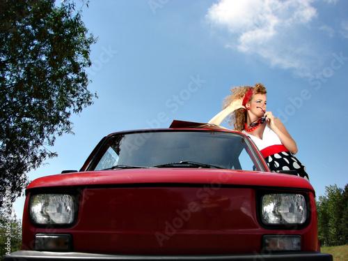 Girl in dress with red comapct car Fototapeta