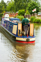Man Steering  Houseboat Along Canal With Dog On Board