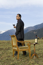 Uomo In Piedi In Mezzo Ad Un Prato Con Un Bicchiere Di Vino