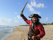 Pirate In Vintage Costume On The Beach With Sword