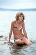 Teenage girl in bikini sitting on a rock in the sea