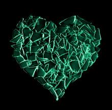 Broken Green Glass Heart Isolated On Black Background.