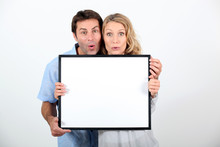 Shocked Couple Stood With Blank Message Board