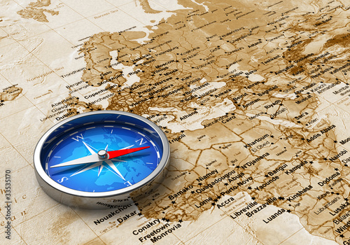 Fototapeta na wymiar Blue metal compass on the old world map