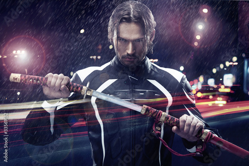 Foto  Man holding a samurai sword on a night city street
