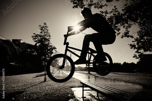 Photo Stands Cycling boy jumping over bench on bmx