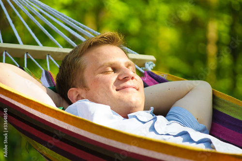 Poster  Young man sleeping in a hammock