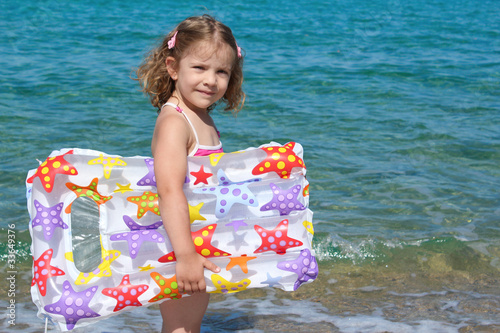 Fotografie, Obraz  little girl with airbed standing in the sea