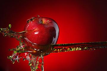 Fototapeta red apple in juice stream