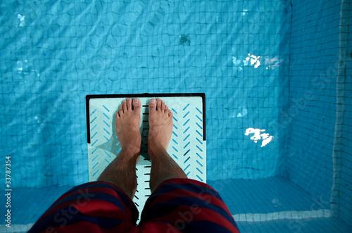 feet on diving board over pool Wallpaper Mural
