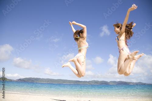 Fotografie, Obraz  浜辺でジャンプする水着を着た2人の女性の後ろ姿
