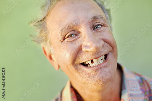 aged toothless man smiling at camera Poster