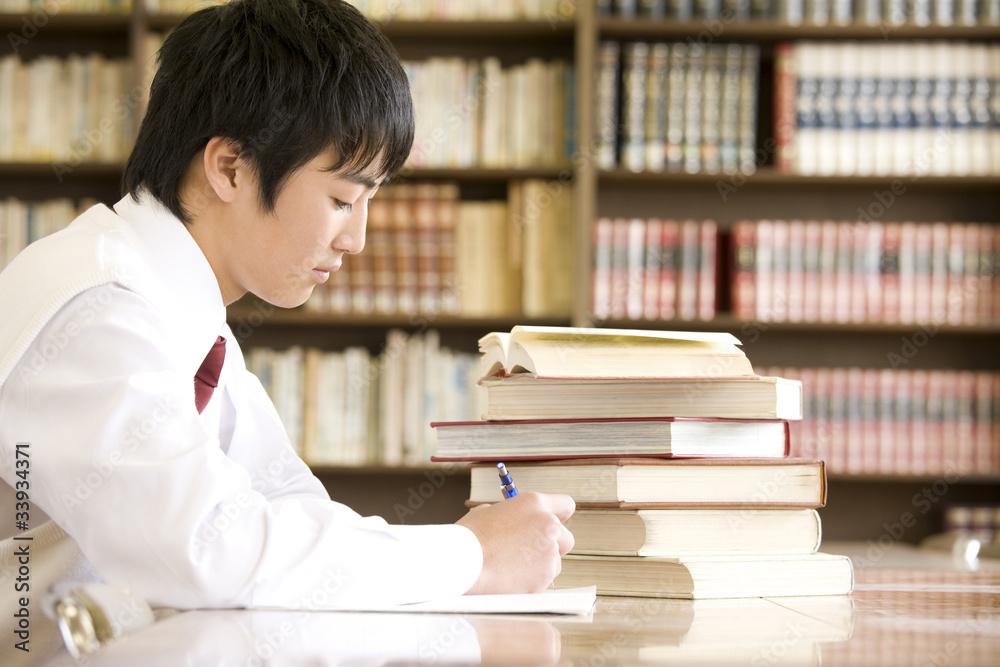 Fototapeta 図書室で勉強する男子中学生