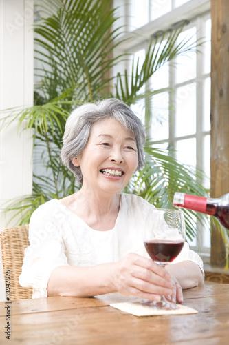 Foto op Canvas Kruidenierswinkel ワインを注がれるシニア女性