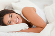 close up of a smiling cute woman lying under sheet