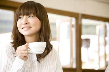 Naklejka カフェでお茶を飲む女性