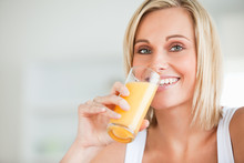 Close Up Of A Smiling Woman Drinking Orange Juice In Kitchen