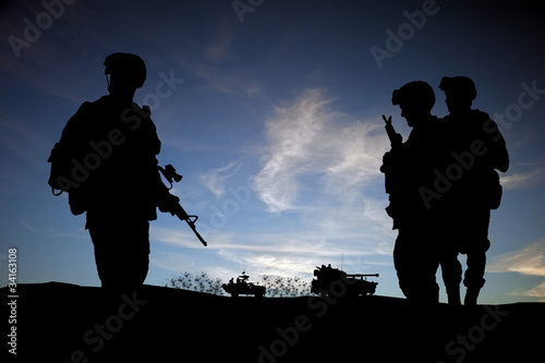 Valokuva  Silhouette of modern soldiers with military vehicles