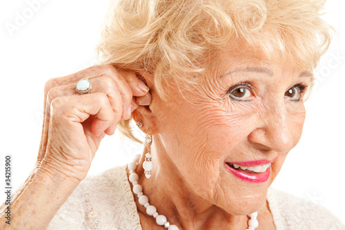 Photo  Senior Woman Inserts Hearing Aid