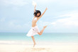 happy young woman jumping on the beach of sea