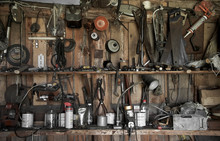 Many Different Old Tools Hanging On A Barn Wall