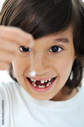 Photo  Lost milk-tooth, cute boy holding his tooth on thread