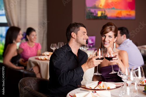 Fotobehang Restaurant happy couple at restaurant table toasting