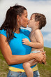 Pretty young hispanic woman kissing a baby boy