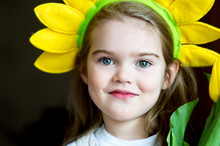 Sunny Child Girl With Yellow Crown On Dark Background