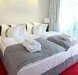 Hotelbett mit leerer weisser Wand am Kopfende