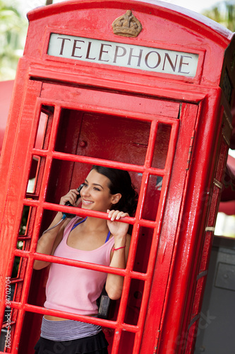 Fotografie, Obraz  Pretty young woman in a vintage red telephone booth