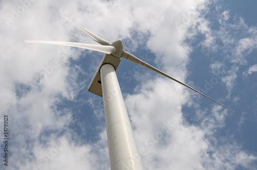 Wind turbine against a sky blue background with clouds - fototapety na wymiar
