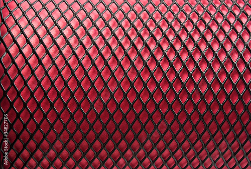 Photo  Metal grid on a red background.