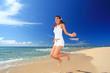 波打ち際でジャンプをする女性