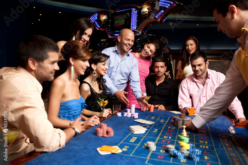 Fotografering happy friends playing roulette in a casino
