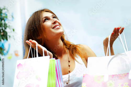 Fotografie, Obraz  Shopping woman with lots of bags smiles inside mall. She is happ