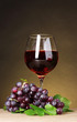 Glass of wine and grapes on yellow background