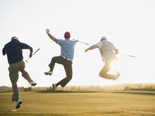 Excited Golfers Jumping In Mid-air On Golf Course
