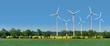 canvas print picture - Windkrafträder in einem Rapsfeld hinter einer Allee