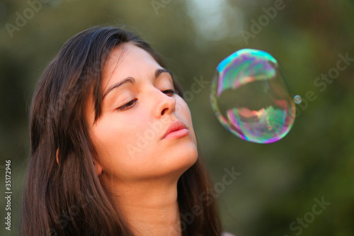 Pretty woman inflating soap-bubbles Canvas Print