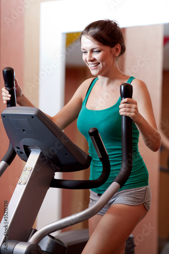 Fotografie, Obraz  Young women in gym on stepper machine