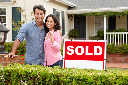 Valokuva  Hispanic couple outside home with sold sign
