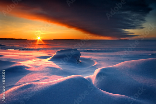 In de dag Nachtblauw Snowy seascape with dark cloud and rising sun