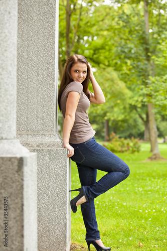 lächelnde hübsche junge Frau im Park lehnt an Säule