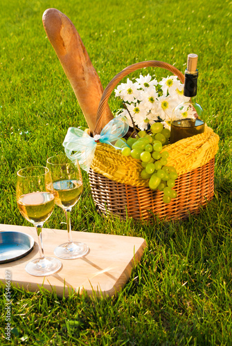 Poster Picnic glasses of white wine and picnic basket