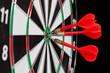 Darts hitting the bullseye on a dartboard