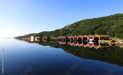 Staande foto Scandinavië Row of red colored boathouses in fjord in Scandinavia