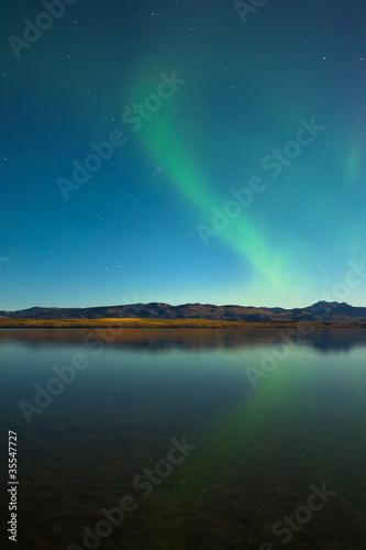 Photo  Northern lights and fall colors at calm lake