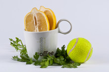 Two Halves Of Lemon In A Cup Of Coffee And A Tennis Ball