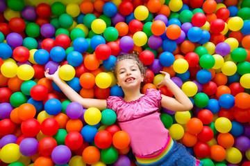 Fototapeta na wymiar child girl on colorful balls playground high view